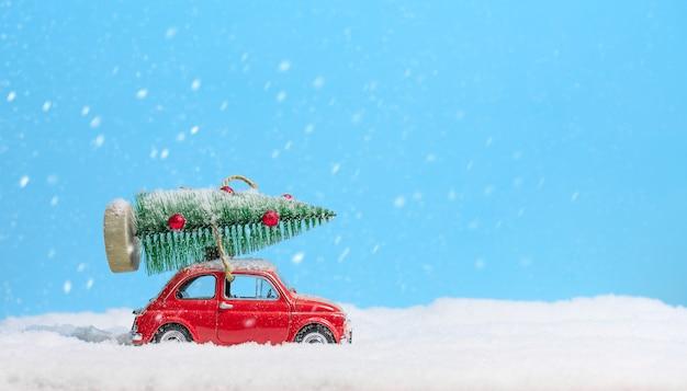 Retro automobile rossa del giocattolo che porta albero di natale sul tetto nella neve su fondo blu. sfondo di natale. carta di vacanze. copia spazio.