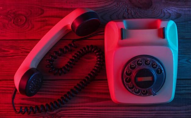 Telefono rotativo retrò su una superficie di legno con luce al neon rosso-blu