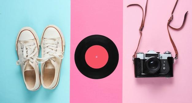 Natura morta retrò con scarpe da ginnastica vecchio stile, dischi in vinile e fotocamera a pellicola vintage