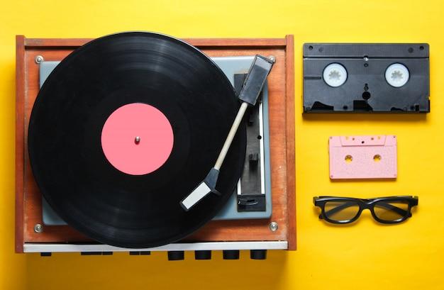 Stile retrò, anni '80, attributi della cultura pop su uno sfondo giallo. lettore in vinile, occhiali 3d, audio, videocassetta.