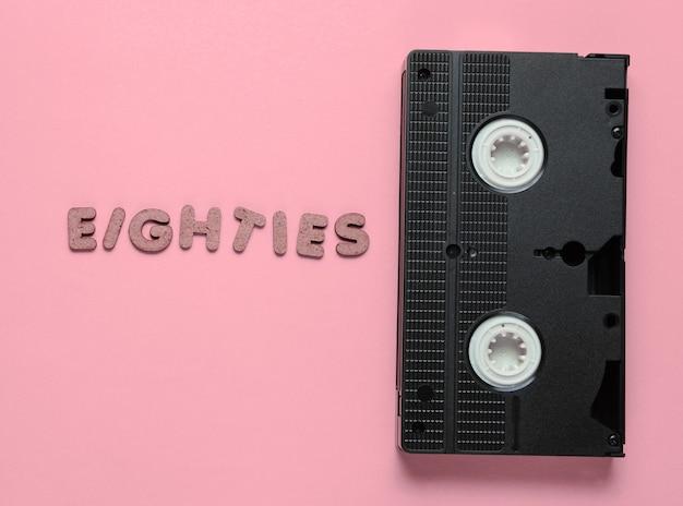Concetto di stile retrò, anni '80. videocassetta su pastello rosa con la parola eighties da lettere in legno