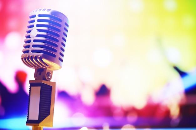 Microfono in stile retrò su sfondo con retroilluminazione. microfono vintage argento per suono, musica, karaoke. apparecchiature per la trasmissione vocale. performance musicale pop e rock dal vivo. messa a fuoco selettiva