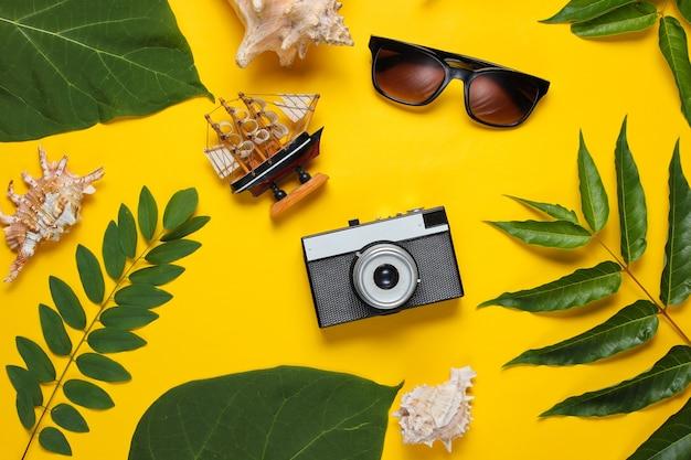 Stile retrò viaggi ancora in vita. fotocamera, occhiali da sole, conchiglie, foglie tropicali verdi. accessori del viaggiatore su sfondo giallo.