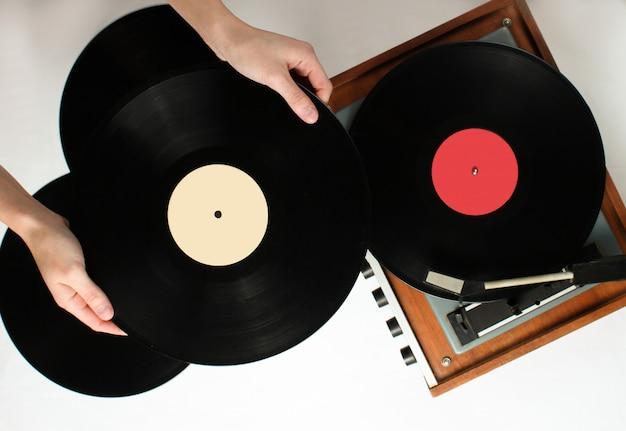 Stile retrò, mani di donna con disco in vinile, lettore in vinile con dischi su sfondo bianco, anni '80, vista dall'alto