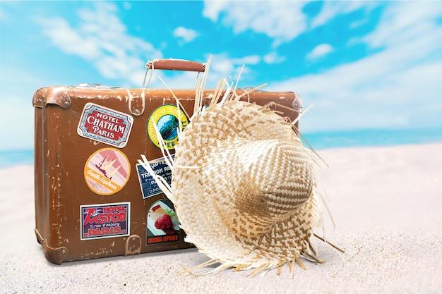 Valigia retrò con cappello da viaggio su sfondo tropicale