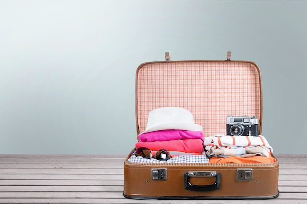 Valigia retrò con oggetti da viaggio sullo sfondo