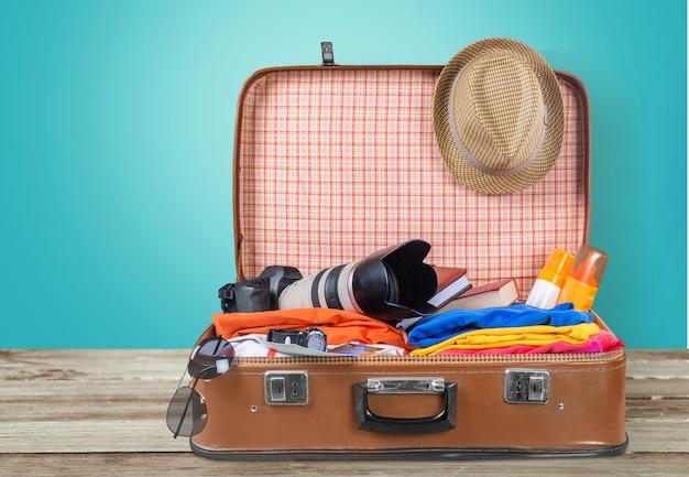 Valigia retrò con oggetti da viaggio su tavola di legno su sfondo naturale