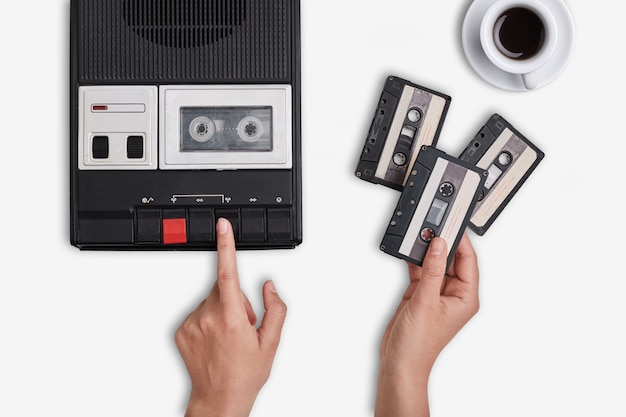 Retro registratore, cassette e tazza di caffè caldo in piedi sulla superficie bianca.