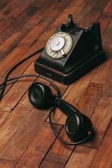 Telefono retrò nero su un pavimento in legno classico alla tecnologia