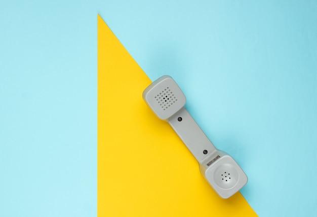 Cornetta del telefono retrò su carta colorata con forme geometriche