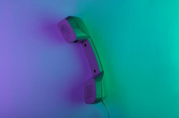 Cornetta del telefono retrò con luce al neon verde e magenta
