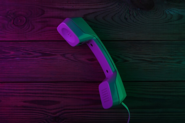 Cornetta del telefono retrò su una superficie di legno con luce al neon verde e magenta