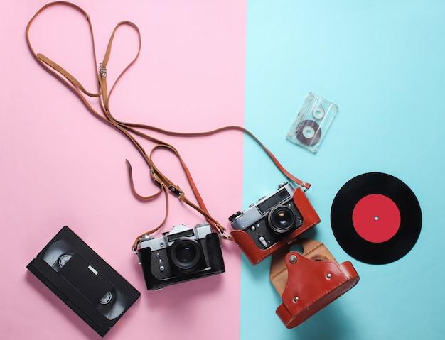 Retro vista dall'alto ancora in vita. disco in vinile, fotocamera a pellicola vintage, cassetta video e audio su rosa blu lay piatto. vista dall'alto