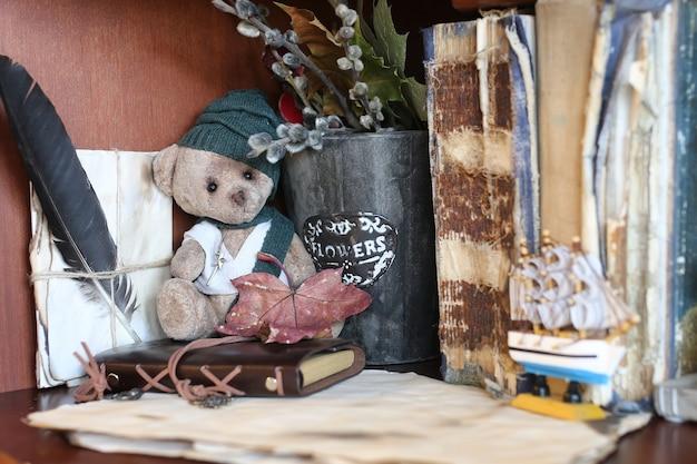 Orsetto giocattolo retrò e vecchi libri con lettera di piume