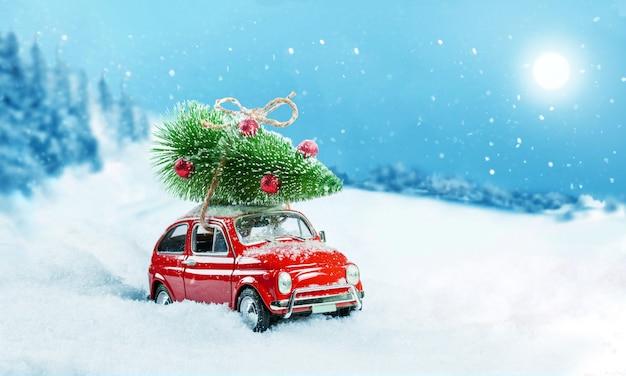 Auto giocattolo retrò che trasporta albero di natale sul tetto nella foresta invernale innevata. sfondo di natale. carta di vacanze.