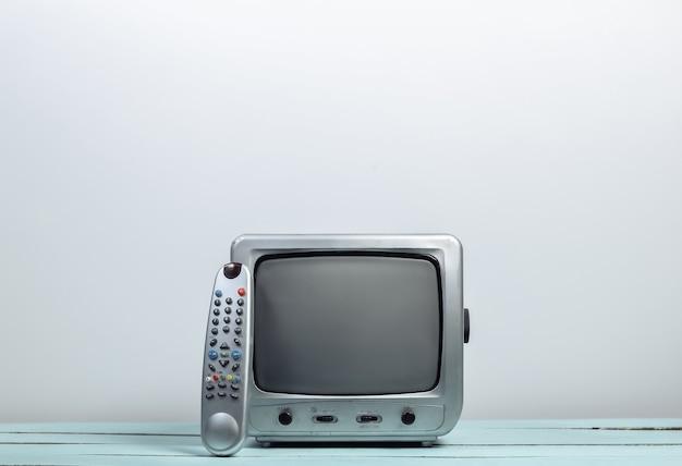 Ricevitore tv retrò con telecomando tv sulla parete bianca
