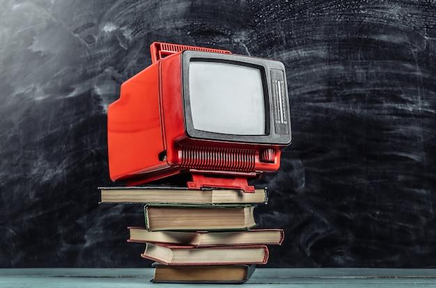 Tv retrò e pila di libri su sfondo lavagna. didattica a distanza televisiva.