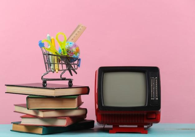 Tv retrò e pila di libri, carrello della spesa con materiale scolastico su sfondo rosa. didattica a distanza televisiva.