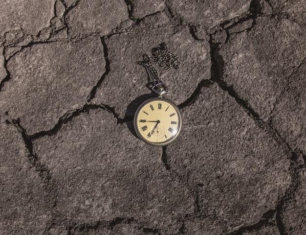 Orologio da tasca antico vintage retrò, giacciono su uno sfondo di terra asciutta.