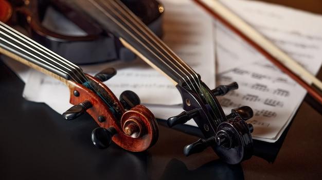 Violino retrò e viola elettrica moderna, primo piano, nessuno. due strumenti musicali a corda classici, taccuino di musica