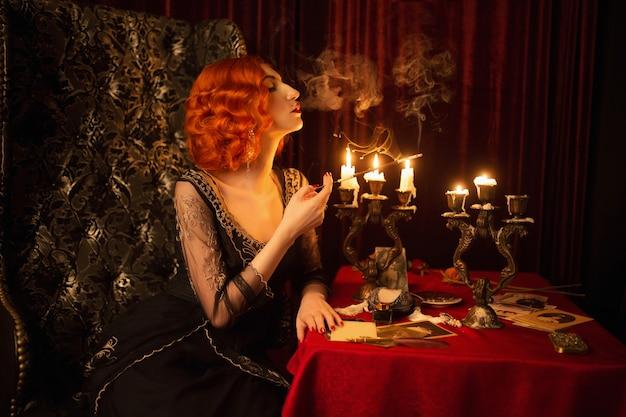 Donna retrò con i capelli rossi in abito vintage nero. donna rossa d'annata con le labbra rosse che fumano sigaretta in boccaglio. noir fashion. le candele bruciano nel candeliere. film noir. fumo di sigaretta. 1920