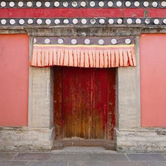 Retrò porta di legno e parete nel monastero di kumbum, tempio ta'er un monastero buddista tibetano nella contea di huangzhong, xining qinghai cina.