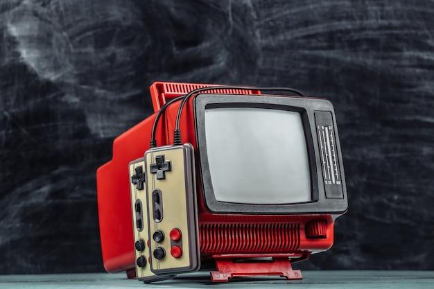Retrogioco. concorso di videogiochi. vecchia tv con gamepad su sfondo lavagna