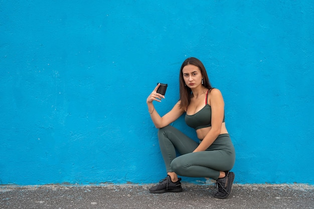 Retty giovane donna in abbigliamento sportivo tenere il caffè. stile di vita sano