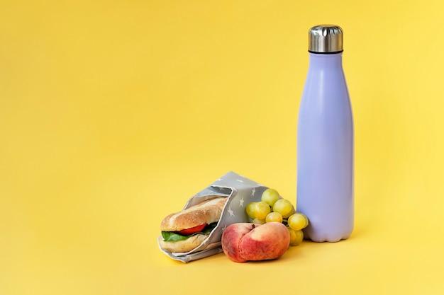 Bottiglia riutilizzabile e involucro di sandwich su sfondo giallo brillante pranzo al lavoro a scuola concept