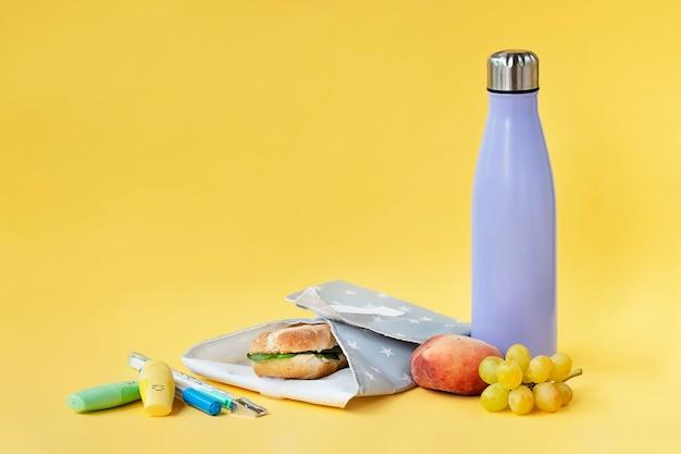 Bottiglia riutilizzabile e involucro a sandwich su sfondo giallo brillante concetto di sostenibilità