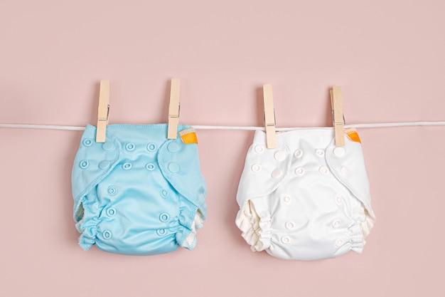 Pannolini di stoffa riutilizzabili che si asciugano su una linea di vestiti. pannolini di stoffa ecologici su sfondo rosa. stile di vita sostenibile. rifiuti zero concetto.