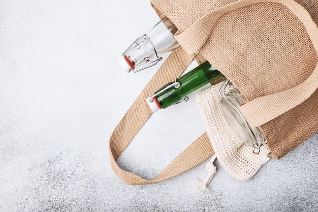 Bottiglie di vetro riutilizzabili e barattoli in sacchetto di juta.