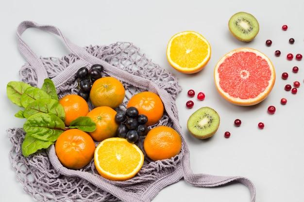 Borsa a rete riutilizzabile con frutti e foglie di bietola sul tavolo
