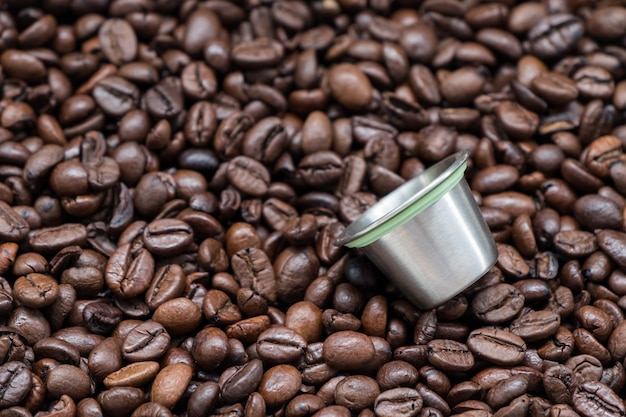 Capsula di caffè riutilizzabile in metallo sul chicco di caffè tostato scuro.
