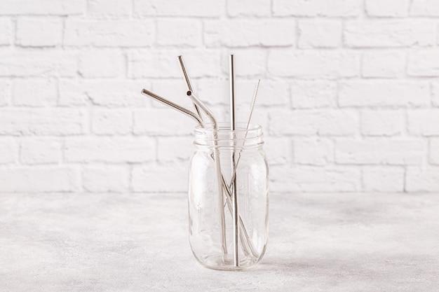 Sraws in metallo riutilizzabili e spazzola per la pulizia in un barattolo