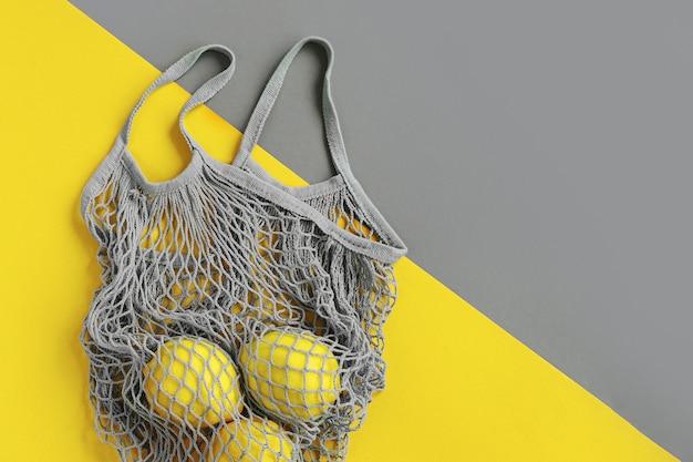 Borsa della spesa riutilizzabile con limoni. colori dell'anno 2021 ultimate grey e illuminating. tavolozza di tendenza dei colori. sfondo elegante