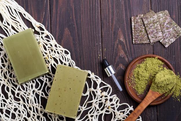 Shopper riutilizzabili con sapone verde oliva fatto a mano e polvere verde su legno scuro. concetto di rifiuti zero. niente plastica.