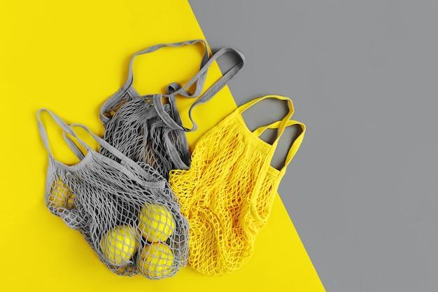 Shopper riutilizzabili con limoni. colori dell'anno 2021 ultimate grey e illuminating. tavolozza di tendenza dei colori. sfondo elegante