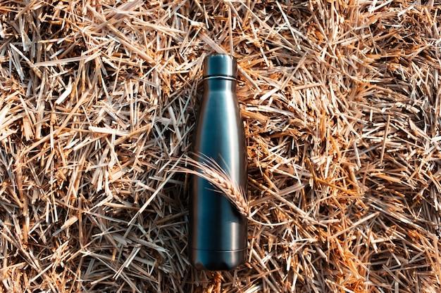 Termo bottiglia riutilizzabile in acciaio sullo sfondo del pagliaio secco.
