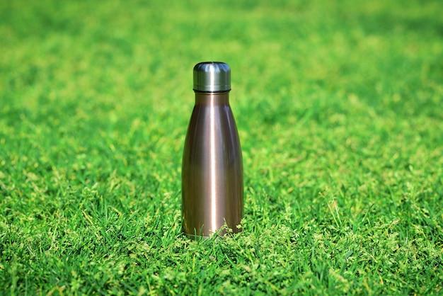 Borraccia termica in acciaio riutilizzabile su erba verde borraccia termica in acciaio d'argento su sfondo di erba sfocata con spazio per le copie Foto Premium