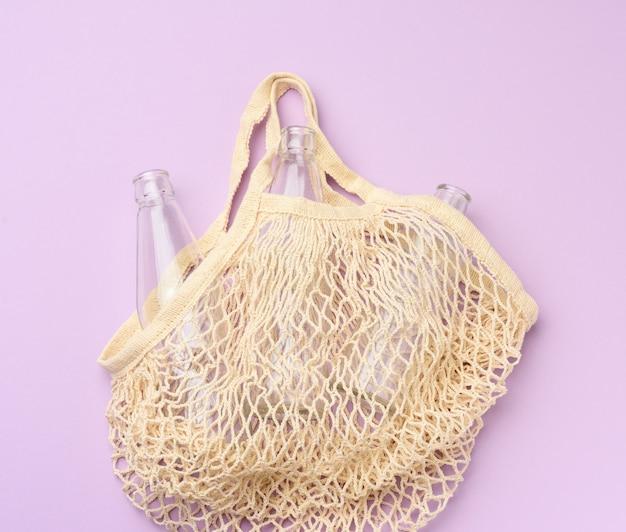 Shopping bag in tessuto riutilizzabile con bottiglie vuote su uno sfondo viola, zero rifiuti