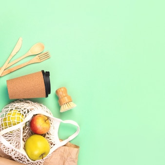 Posate in legno riutilizzabili, tazza di sughero e sacchetto della spesa con mele. spazzola per piatti e carta da imballaggio kraft, forchetta ecologica, coltello, cucchiaio su sfondo quadrato verde menta. rifiuti zero concetto. copyspace.