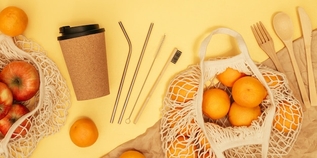 Posate in legno riutilizzabili, tazza di sughero e sacchetto della spesa con frutta sulla bandiera gialla. concetto di rifiuti zero.