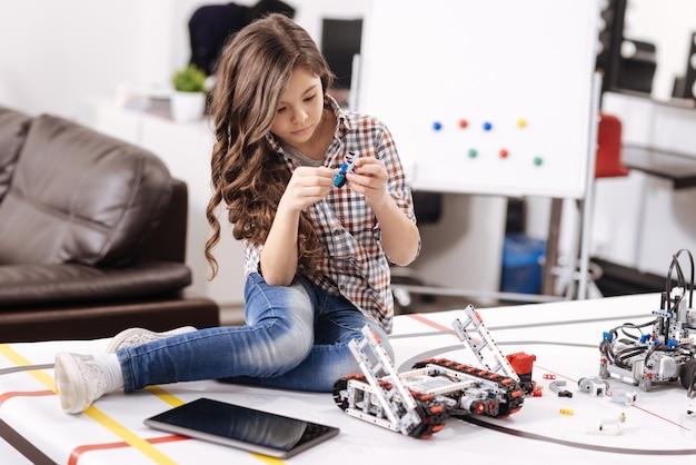 Rivelando il mio talento. ragazza capace e intelligente coinvolta che si siede nel laboratorio di robotica e tiene i dettagli del robot informatico mentre esprime interesse