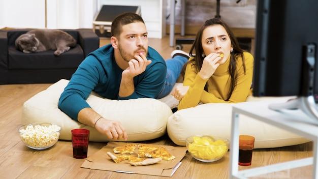 Inquadratura rivelatrice di una giovane coppia che guarda la tv seduta sul cuscino per terra che mangia la pizza mentre il gatto dorme.