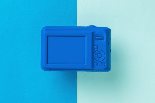 Il retro della fotocamera blu su una superficie bicolore. attrezzatura elegante per riprese di foto e video.
