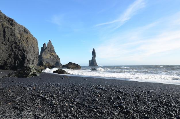 Reynisdrangar pila di mare al largo della spiaggia di reynisfjara con onde.
