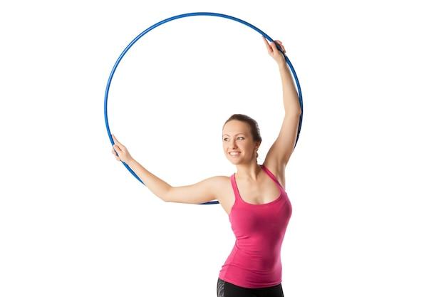 Ginnastica ritmica donna con cerchio in alto e pendente con grazia a destra.