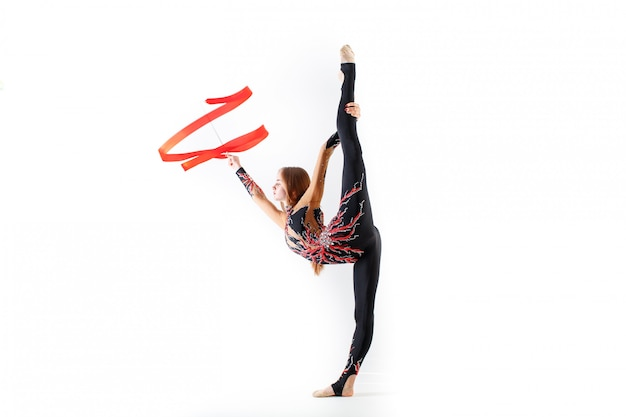 Ginnastica ritmica. giovane donna della ginnasta con il nastro rosso su bianco