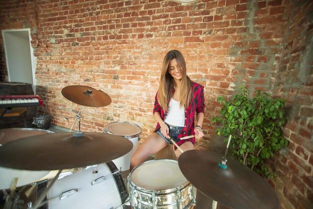 Ritmo. studio musicale domestico, bella donna che registra musica, canta e suona la batteria mentre è seduta sul posto di lavoro in soppalco oa casa. concetto di hobby, musica, arte e creazione. creazione del primo singolo.